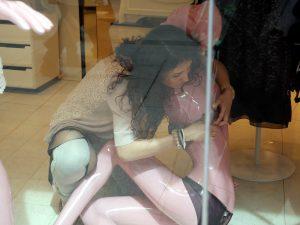 vendedora poniendo un corpiño a un maniquin